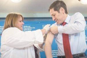 """Dr. Thomas Frieden, director of the Centers for Disease Control and Prevention, received a flu shot from Sharon Bonadies at the conclusion of a news conference at the National Press Club in Washington. """"Vaccination is the single most important step everyone 6 months of age and older can take to protect themselves and their families against influenza,"""" said Frieden. (AP Photo)"""