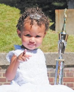 Baby pageant winner Aubri Thompson pointed as she rode through the parade.