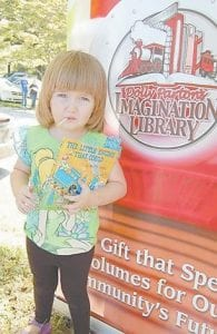"""Micah Boggs holds """"The Little Engine That Could"""", a book she received when she registered for the Imagination Library."""