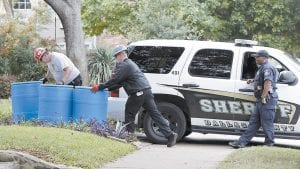 Protect Environmental workers moved disposal barrels to a staging area outside the apartment of a healthcare worker who treated Ebola patient Thomas Eric Duncan and tested positive for the disease in Dallas. (AP Photo)