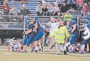 Letcher Central's Jacob Kiser, pictured being held back by teammate Zane Blair, was among players ejected after tempers flared when a Harlan County defensive back slammed an LCC player to the ground. (Photo by Chris Anderson)