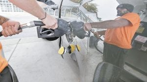 Dana Ripley, of Winthrop, Mass., filled the gas tank of his truck at a service station in Andover, Mass., recently. A swoon in the price of oil is lowering fuel bills for drivers, shippers and airlines, but it is not without downsides for both the U.S. oil boom and the broader economy. (AP Photo)