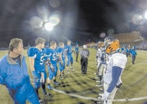 Above, players and coaches gathered for the coin toss before Letcher County Central's game with Madison Southern. Below right, the Cougars' defense was able to keep Southern's Damian Harris, believed by many observers to be the nation's top schoolboy runner, bottled up during the limited action he saw after returning from injury. LCC advances to play Pulaski County this Friday night. (Photos by Brandon Meyer/B. Meyer Images)