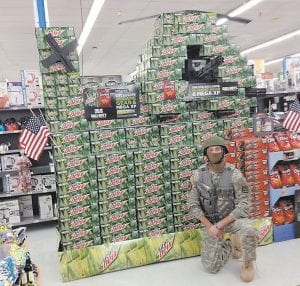 HELICOPTER DISPLAY WINS PRIZE — Austin Mollett, a Pepsi account representative, posed in front of a creative store display that he and Kenneth Ratliff, a Pepsi manager, assembled inside the Whitesburg Walmart in late October.
