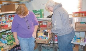 Sisters Geraldine McDonald and Shirley Combs pack a box of food at the Letcher County Food Pantry. Today (Wednesday) is the last day McDonald and Combs will volunteer at the food pantry. Geraldine McDonald and her husband Roger and Shirley Combs and her husband Buford are moving to North Carolina in a couple of weeks.