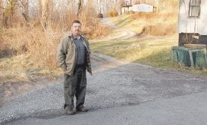 """New Jenkins Mayor Todd Depriest stands next to what he calls a """"skirt"""" of blacktop that was laid down two years ago in the Wheaton Hollow area after water line construction. On December 3, 2012, Depriest wrote the City of Jenkins a check for $1,387.84 for a stretch of blacktop that was put down on a private driveway leading to his home on Lucky Hill. The check was later returned by the bank for non-sufficient funds and has never been paid. Depriest now says he doesn't owe the money. (Eagle photo)"""