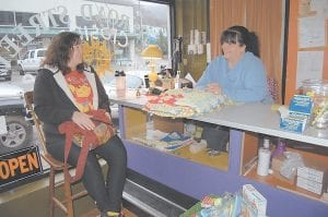 "'THEY MISSED OUT' — Pat Spears of Kona (left) and Kae Fisher talked last week after Spears bought a vintage homemade quilt, a hair bonnet and an aluminum pan from Railroad Street Mercantile. ""Her stuff was priced reasonably,"" said Spears. ""She is friendly and outgoing. If you are looking for something unique, this is the place to find it. I don't know why more people didn't take advantage and come here. They missed out."" The store is scheduled to close at the end of this month. (Photo by Sally Barto)"