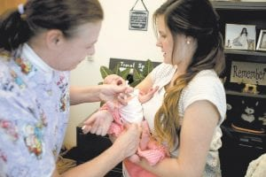 Nurse Bonnie Hardy gave McCall Messick a measles vaccination while McCall's mother, Amy, held her at the Utah County Health Department in Provo recently. (AP Photo)