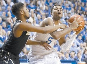 Kentucky's Andrew Harrison, right, is fouled by Vanderbilt's Shelton Mitchell during the first half of an NCAA college basketball game in Lexington Tuesday night. (AP Photo/James Crisp)