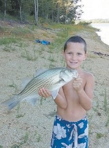Luke Polly, 8, must spend at least eight weeks in a Memphis, Tennessee hospital undergoing chemotherapy treatments before he can get back to catching fish like this one he was photographed with last summer.