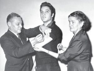 CALLING ON ELVIS — In this Oct. 28, 1956 photo, Elvis Presley receives a Salk polio vaccine shot in New York City from Dr. Harold Fuerst, left. At right is Dr. Leona Baumgartner, commissioner of the New York City health department. (AP Photo)