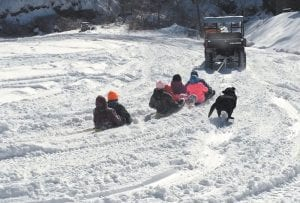 A group including Ashley, Kerrigan and Paylan Bolling, Hailey Pease and Emma Fox enjoyed a ride across a snow-covered lot Tuesday as their sleds were pulled by an ATV as a pet dog tagged along.