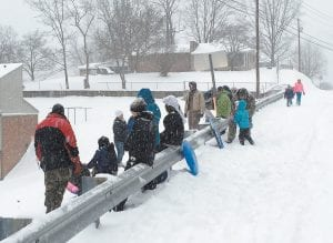 Parents and children looked on as other rode sleds down a steep hill in West Whitesburg Wednesday afternoon as Letcher County was being pelted by what would be at least a foot of snow.