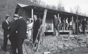 In April 1964, President Lyndon B. Johnson and his wife leave the home of Tom Fletcher, father of eight, who told Johnson he had been out of work for nearly two years in the community of Inez in Martin County, Ky. (AP Photo)
