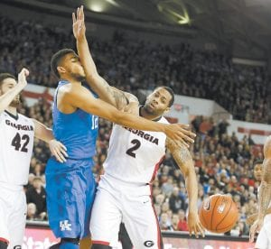 Kentucky forward Karl-Anthony Towns (12) and Georgia forward Marcus Thornton (2) battles for a rebound in the first half of Tuesday's game in Athens, Ga. (AP Photo/John Bazemore)