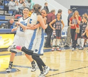 THRILL OF VICTORY, AGONY OF DEFEAT — Letcher Central's Courtney Brock hugged teammate Cheyanne Stidham, while teammate Kristina Bentley looked on after the Lady Cougars' championship victory over Knott Central last last week. Stidham led all scorers in the game, scoring 23 points. She was also 12 for 14 from the free throw line in the game and was named the tournament Most Valuable Player. Among the dejected Knott Central players was leading scorer Kristen Waugh (22). The Lady Cougars defeated Jackson City in the opening round of 14th Region Tournament play Monday night, 52-41. The Lady Patriots also advanced to the regionals and played Leslie County last night. (Photo by Chris Anderson)