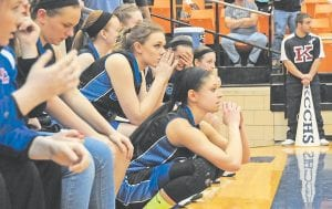 Letcher Central's (front center) Courtney Brock and teammates watched nervously as Brock's replacement, Shelby Hall, shot free throws late in the game. Hall entered the game after officials called a double technical foul on Brock and a Knott Central player, resulting in Brock's fifth foul. Hall hit one of the two shots, which was monumental in the Lady Cougars' overtime win. (Photo by Chris Anderson)