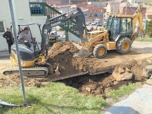 — Whitesburg city employees were busy late Tuesday afternoon repairing a collapsed sewer line at the intersection of Cowan Street and College Drive in downtown Whitesburg. In this photo, Ken Sexton Jr. is seen operating a track hoe while City Police Chief Tyrone Fields looks on. (Eagle photo)