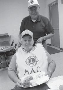 NEW LION — Lion Sam Quillen welcomes new Neon Community Lions Club member Macky Cook to the club with his very own Lions bib. The Neon club meets the first and third Tuesday in the fellowship hall of the First Church of God.