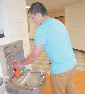 Malcolm Bailey, an eighth grader at Whitesburg Middle School, refills his aluminum water bottle with filtered water now available at three Letcher County schools.