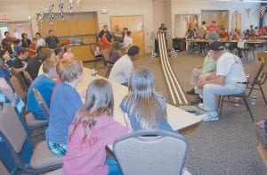 Above, a crowd looked on as Jimmy Craft, of Ice, who served as offical starter, attached a wheel to a Pinewood Derby-style car before it raced in the Awana Grand Prix at the Letcher County Extension Office in Whitesburg on April 29. Below, cars and trucks were lined up on the judge's table at the Letcher County Extension Office on April 29. Children who participate in Awana programs at Colson and Premium Baptist churches assembled cars to race in the Awana Clubs event. (Photos by Sally Barto)