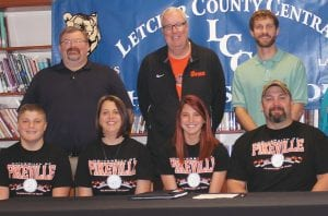Two members of Letcher County Central High School's girls' track team have signed to continue their careers with the University of Pikeville women's track team next season. Pictured above, Brittney Buttrey (front row, second from left) is seated between her parents, J.J. and Nicole Buttrey, as Letcher Central Principal Stephen Boggs (back row, from left), UPike Coach John Biery and LCC Coach Winston Lee look on during a recent signing session. Brittney's brother, Jayson, is seated far left. In the photo at bottom, UPike's Biery assists LCC's Brittney Day as her parents, Darrell Day and Brenda Day look on.