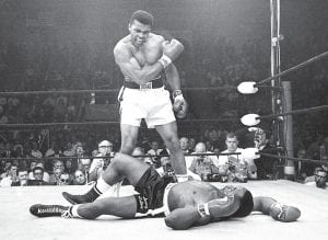 Associated Press photographer John Rooney won an award for best sports photo of 1965 with this iconic image showing 23-year-old Cassius Clay standing over his felled heavyweight opponent, Sonny Liston. (AP Photo)
