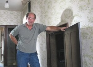 Karl Kissner posed in front of the door to an attic in his grandfather's old home on July 10, 2012, where he and a cousin found a collection of century-old baseball cards in Defiance, Ohio. (AP Photo)