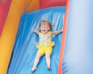 — Allison Anderson smiled as she went down one of the inflatable play features at the Kids Day celebration in the Jenkins City Park on Saturday. The event provided food, fun and entertainment for kids of all ages. The event is held annually by the Letcher County Kids Day Committee and the city.