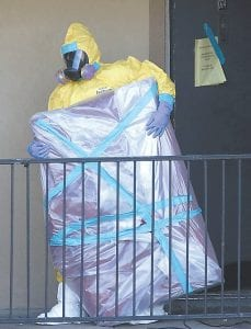 In this Oct. 6, 2014 file photo, a hazardous material cleaner removed a wrapped item from the Dallas apartment where Thomas Eric Duncan, the Ebola patient who traveled from Liberia to Dallas, stayed. Most people will experience at least one wrong or delayed diagnosis in their lifetime, concludes an alarming report. (AP Photo)