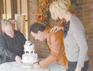 Donna Ball watches as Paul Wilson cuts the cake she made. Jenna Elfman is pictured at right. (Photo by Ron Flanary)