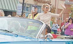 Jenna Elfman waves and recorded her view of the parade on a smart phone.