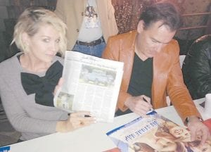 Jenna Elfman holds up a copy of The Mountain Eagle that she signed during an autograph session at the original home of John Fox Jr. Paul Wilson is pictured beside her.