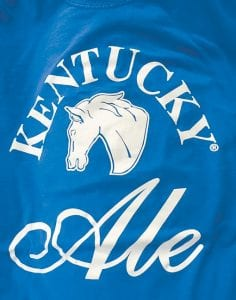 """Other Commonwealth-based companies use the name """"Kentucky"""" in registered trademarks. These photos show the front and back of a T-shirt given away last March at a University of Kentucky basketball game. The shirt advertises a beer brewed by Alltech, a Lexington company that is represented by the King & Schickli law firm — the same firm that wrote the initial letter October 12 demanding that Whitesburg's Kentucky Mist Distillery abandon its effort to trademark its logo."""