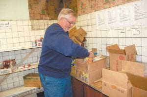Volunteer Randy Craft, of Whitesburg, placed canned beans in a box of food at the Letcher County Food Pantry. The number of people picking up boxes has increased lately as more people are laid off from work and as 2015 is coming to an end.