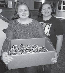 Kayla Trotter, 13, of Mayking, presents Bethany Allen, 17, of Mayking, from New Beginnings Assembly of God Church in Jenkins, with 435 bracelets she made to help fill shoeboxes for Operation Christmas Child.