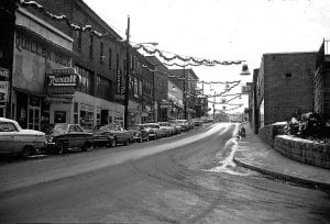 Main Street parking spaces were filled but the sidewalks were empty when this photograph of downtown Whitesburg was taken after a light snowstorm during the Christmas shopping season of 1965. (Photo by John Engle)