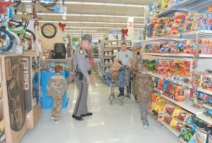 Kentucky State Police Trooper MIchael Burton and Whitesburg Walmart store manager Roger Collier helped two young boys pick out toys during KSP Post 13's annual Shop with a Trooper event on December 4. The event benefitted 76 children from Letcher, Knott, Leslie, Perry and Breathitt counties, with each child selecting $125 worth of items from the Whitesburg store. (Photo by Sally Barto)