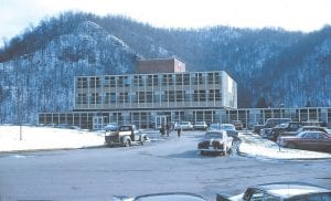 The Whitesburg Appalachian Regional Hospital had been around for about nine years when Dr. John Engle took this photograph in the winter of 1965. The hospital, built by the United Mine Workers of America, officially opened for business as Whitesburg Memorial Hospital on March 23, 1956. Its first inpatient was Mrs. Verdie Day of Mayking. On April 2, 1956, the first baby was delivered at the hospital, a girl born to Mr. and Mrs. Joe Varson of McRoberts. In October 1963 — eight years after it opened — ownership of the Whitesburg hospital and five other UMW-owned hospitals was assumed by Appalachian Regional Hospitals Inc., a non-profit corporation set up under sponsorship of the United Presbyterian Church Board of National Missions. Dr. Engle, the photographer who took this photo, joined the hospital staff as a general practitioner in September 1964 after being assigned to the region by the Mennonite Central Committee, a body of the United Mennonite Church.