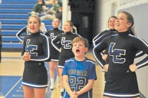 LENDING A VOICE — LCC cheerleaders Taylor Herron and Emily Johnson got a little help on the front line during Monday's game from Peyton Hammonds, son of LCC boys' coach Robert Hammonds. Peyton helped cheer the Cougars on to a 71-37 win over visiting Eastside, Va. (Photo by Chris Anderson)