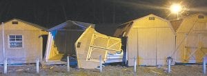 — Two Amish-style wooden barns were destroyed and three other barns damaged Sunday night when a woman ran her vehicle off U.S. 119 at Ermine and into a lot occupied by Kingdom Comes Barns. The driver of the vehicle told police she was forced off the road, lost control and overcorrected her vehicle before crashing into ther barns. Kingdom Come officials believe damages to their property will total at least $12,000. They have not been told whether the driver had liabilty insurance.The wreck is still being investigated by Kentucky State Police. (Photo by Ben Gish)