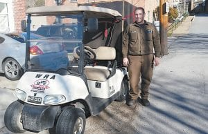 UPS employee Kyle Thacker stood beside a golf cart used to deliver packages in downtown Whitesburg, in front of The Mountain Eagle office. The golf cart is being used during the busy Christmas season to speed up the delivery of packages. (Photo by Lisa Herman, UPS health and safety supervisor)