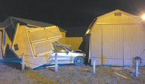 This was the scene at Ermine Sunday night after a vehicle crashed through a fence and buildings at Kingdom Comes Barns. The driver of the vehicle told police she was forced off U.S. 119 before crashing into two barns and damaging two others. (Photo by Ben Gish)