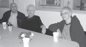 Ed and Betty Pike and Claudia Banks posed for a picture at a Christmas party for the Ermine Center seniors.
