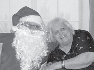 Residents of Letcher Manor enjoyed a Christmas party on December 23 with family and friends. The Pure and Simple Band performed at the party, and Santa Claus (Tim Caudill) also visited. Each resident received a gift and a throw. Pictured with Santa Claus is Viola Caudill.