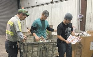 """David Day, who is a full-time worker at the City of Whitesburg Recycling Center, and Rob Sexton and Gary Sexton, Whitesburg City employees, were busy Tuesday afternoon separating discarded mail circulars and old newspapers for recycling. """"I encourage everyone to recycle to save the environment,"""" said Whitesburg Mayor James W. Craft, who announced the city's plan last week to try to save the Letcher County Recycling Center from closing. The center is located at the mouth of Cowan. (Eagle photo)"""