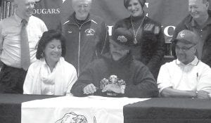 Letcher County Central High School senior running back Jaylyn Williams signs a letter of intent to play football at Morehead State University. He is seated between his parents, Janice and Wendell Williams. Behind the Williamses are (left to right) Athletic Compliance Officer Mike Melton, former LCCHS Athletics Director Ozz Jackson, LCCHS Principal Gracie Maggard and Mike Holcomb, former LCCHS football coach.