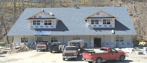 Two new Whitesburg buiidings at different stages of construction will soon have an effect on retail sales and the health care profession in Letcher County. The photo above shows a new structure at Pine Mountain Junction that is already home to the Mountain Instant Care clinic and will soon be the new location of Pine Mountain Outfitters, now located at Ermine. The building, which is owned by the Childers family and shares a parking lot with Pine Mountain Grill, will also house a second retail store. At left is a building in West Whitesburg being built as the new home of East Kentucky Physical Therapy, which will soon vacate its current location beside Food City to make room for an expansion by the grocery company that is expected to cost at least $1 million. (Eagle photos)