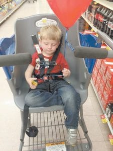 While Stacy Wright shopped at Food City in Whitesburg on Monday, her four-year-old son Logan Wright enjoyed riding in Caroline's Cart, a shopping cart designed to carry children and adults with special needs.