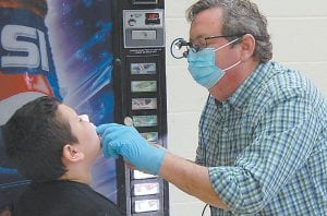 Caleb Eldridge, a third grader at Letcher Elementary School, was examined by Dr. Charles Tritle.